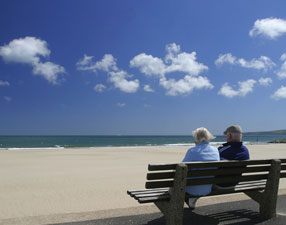 retired couple sitting on a bench at the beach