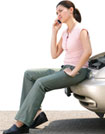 woman sitting on her car bumper and making a call