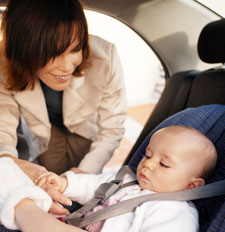 Mom strapping her infant into a car seat
