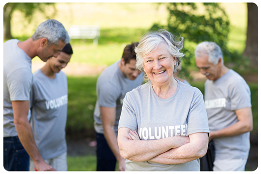 A senior woman stands smiling with a group of volunteers wearing volunteer t-shirts